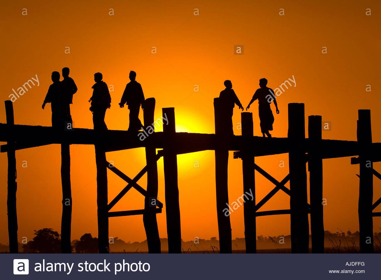 Sagome di persone che camminano attraverso la mitica U Bein ponte sopra il fiume Ayerwaddy al tramonto Amarapura Immagini Stock