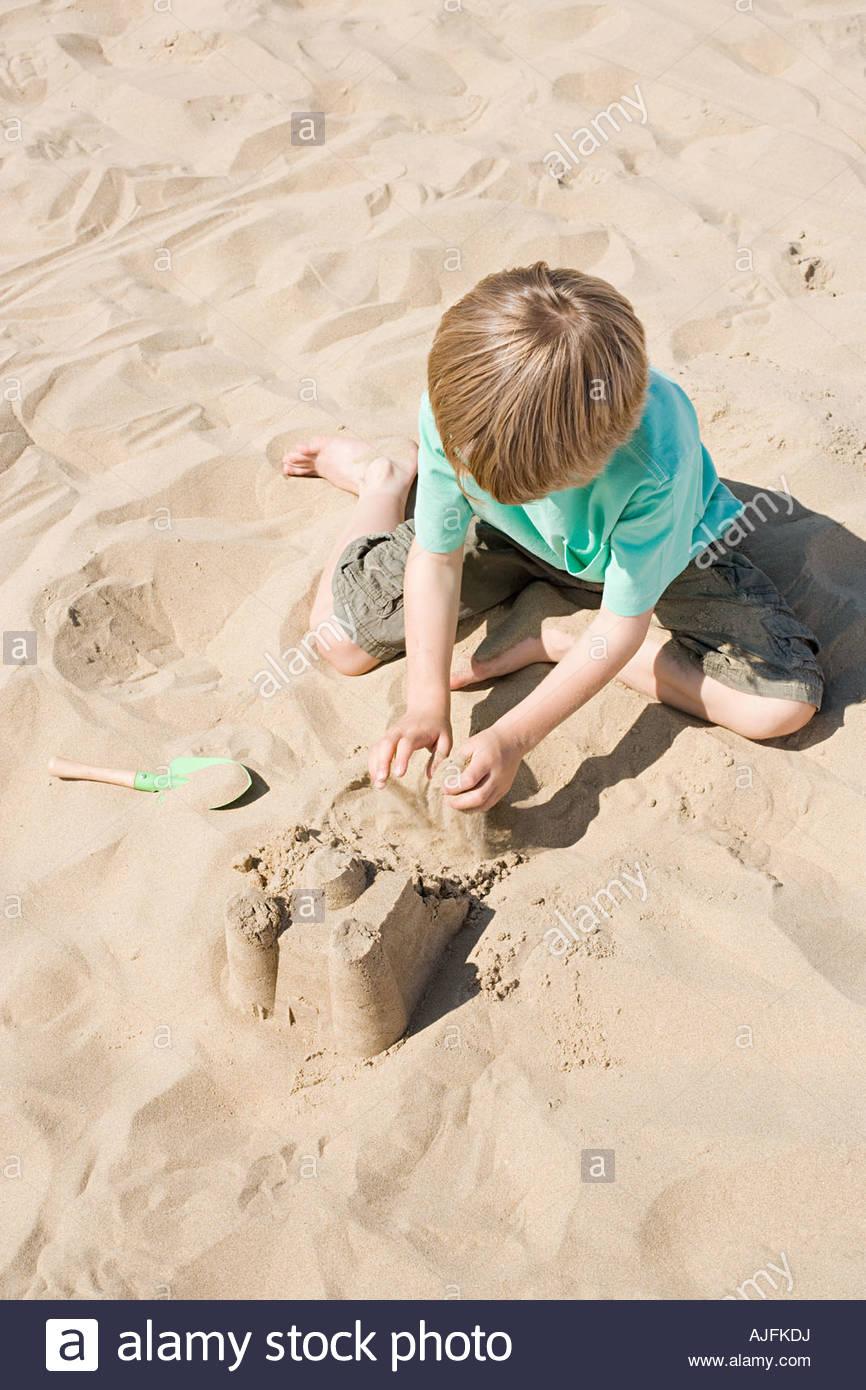 Un ragazzo facendo un castello di sabbia Immagini Stock