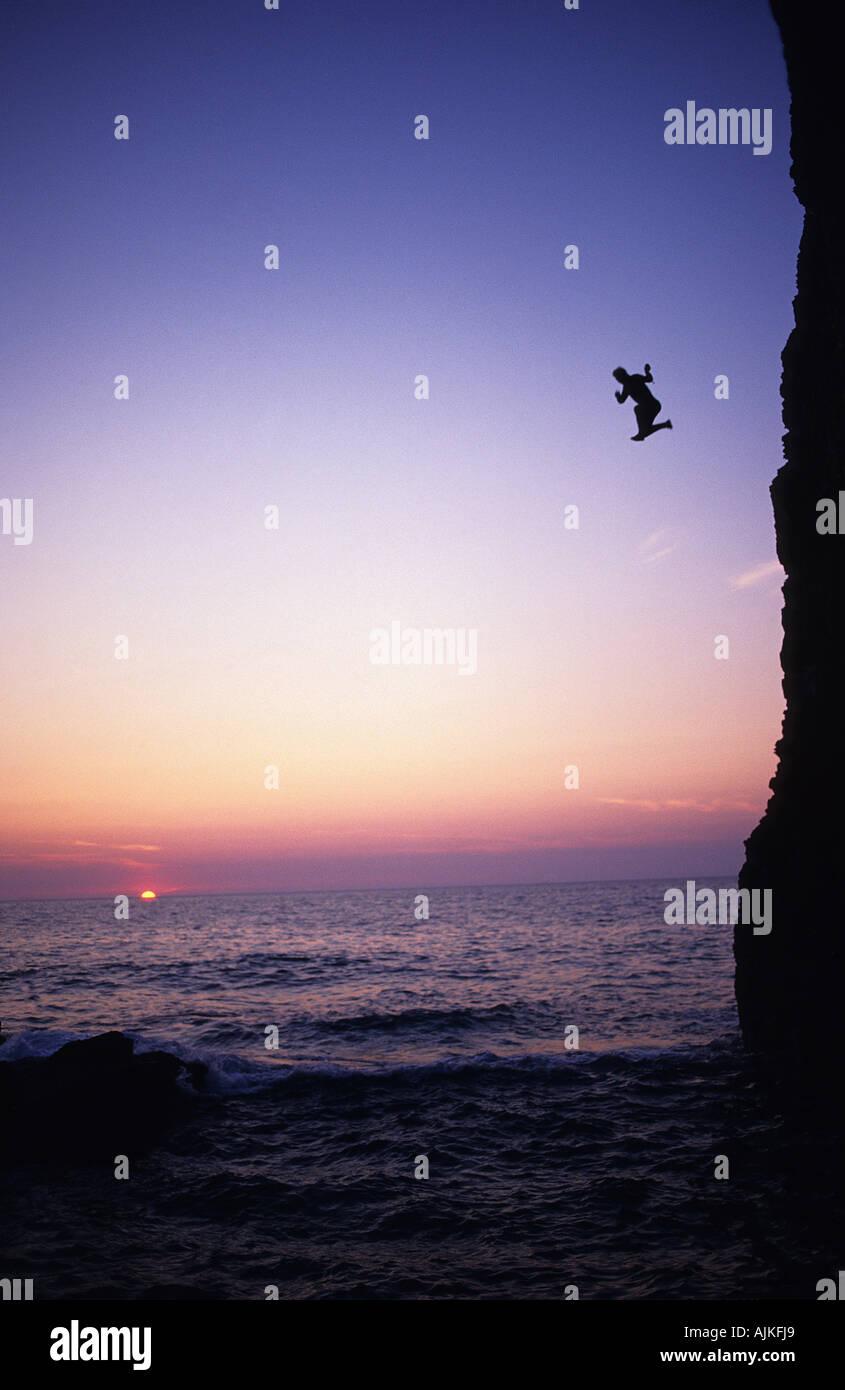 L'uomo corre e salta fuori da una scogliera in sunset Immagini Stock