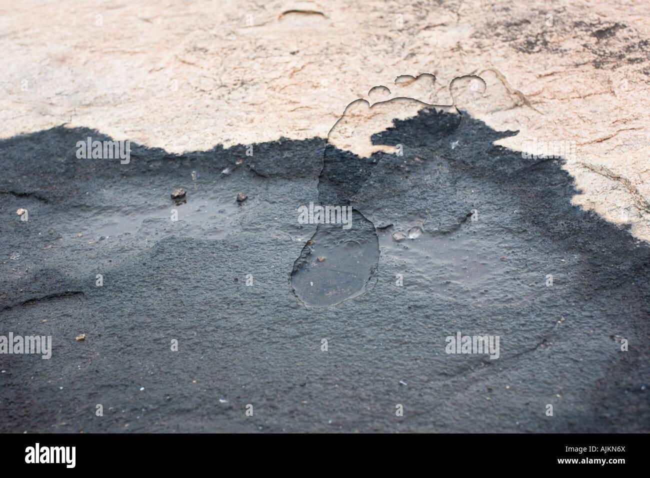 Footprint sovrapposti nella roccia per rappresentare le emissioni di anidride carbonica Immagini Stock