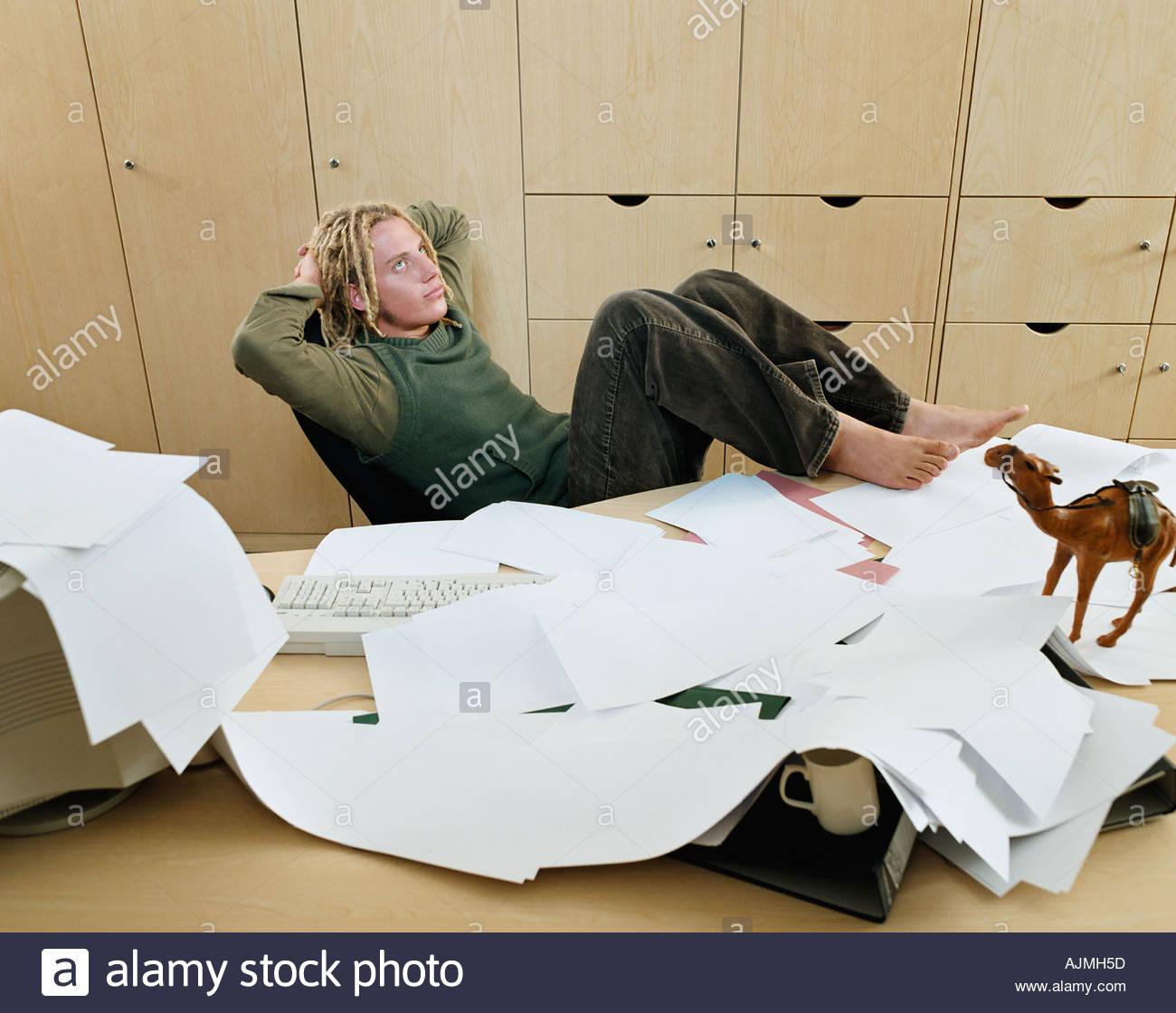 Uomo con scrivania caotica Immagini Stock