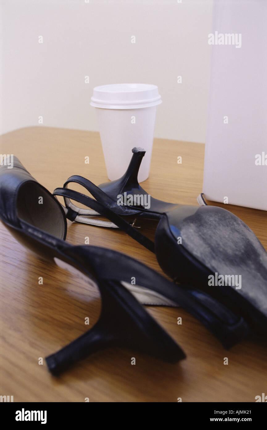 Alta scarpe con tacco e cup su una scrivania Foto   Immagine Stock ... df0bda5346e