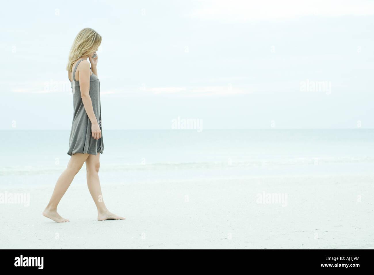 Giovane donna camminando sulla spiaggia, tramite telefono cellulare a piena lunghezza Immagini Stock