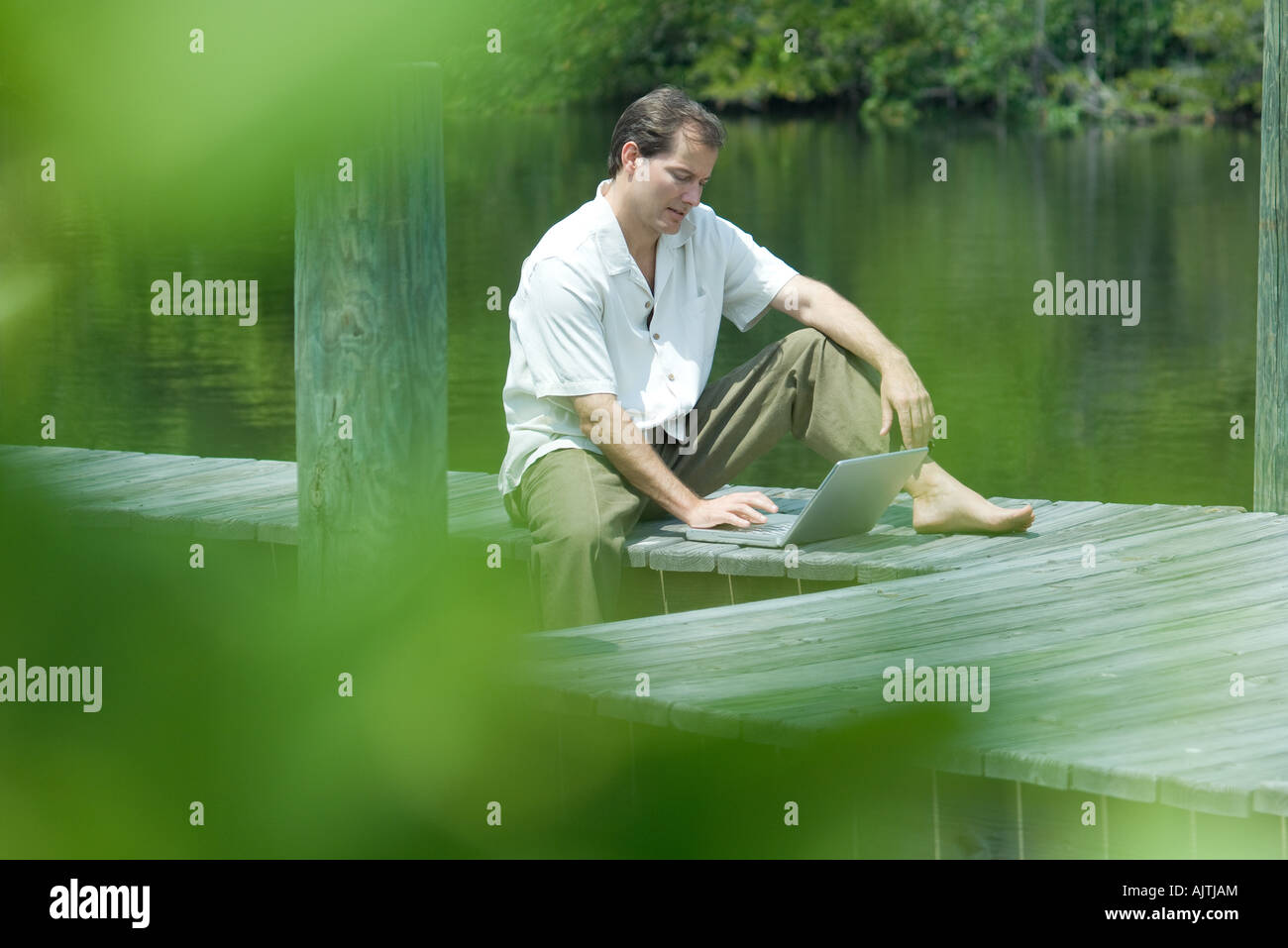 Uomo seduto sul dock tramite computer portatile, vista attraverso il fogliame Immagini Stock
