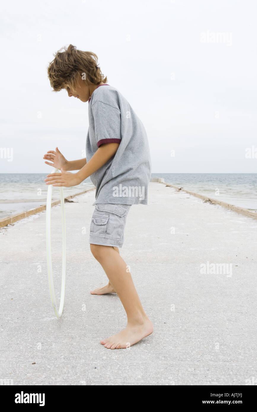 Ragazzo in piedi sul molo, giocando con il cerchio di plastica, vista laterale a piena lunghezza Immagini Stock