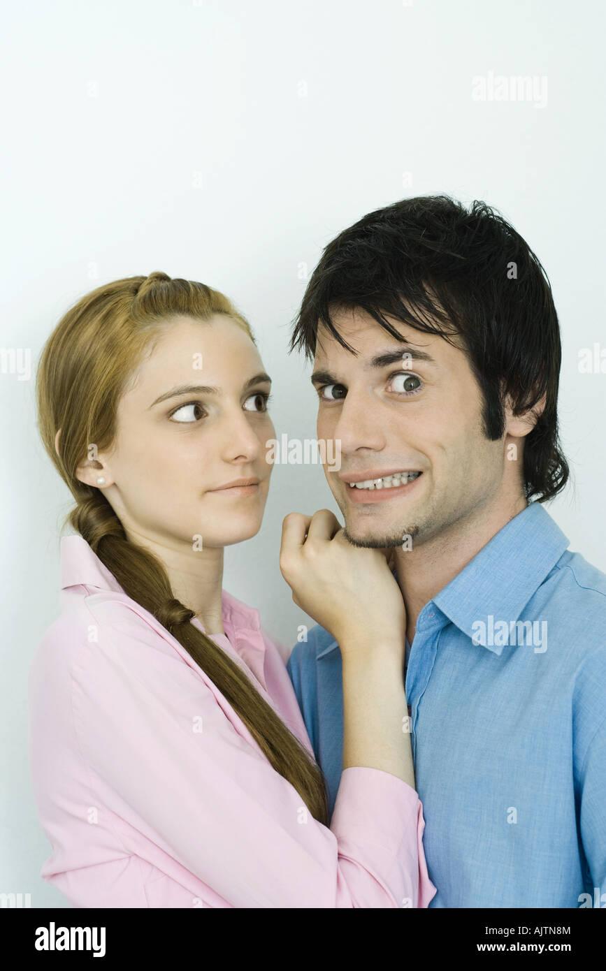 Coppia giovane insieme, l'uomo facendo facce a fotocamera, donna che guarda l'uomo Foto Stock