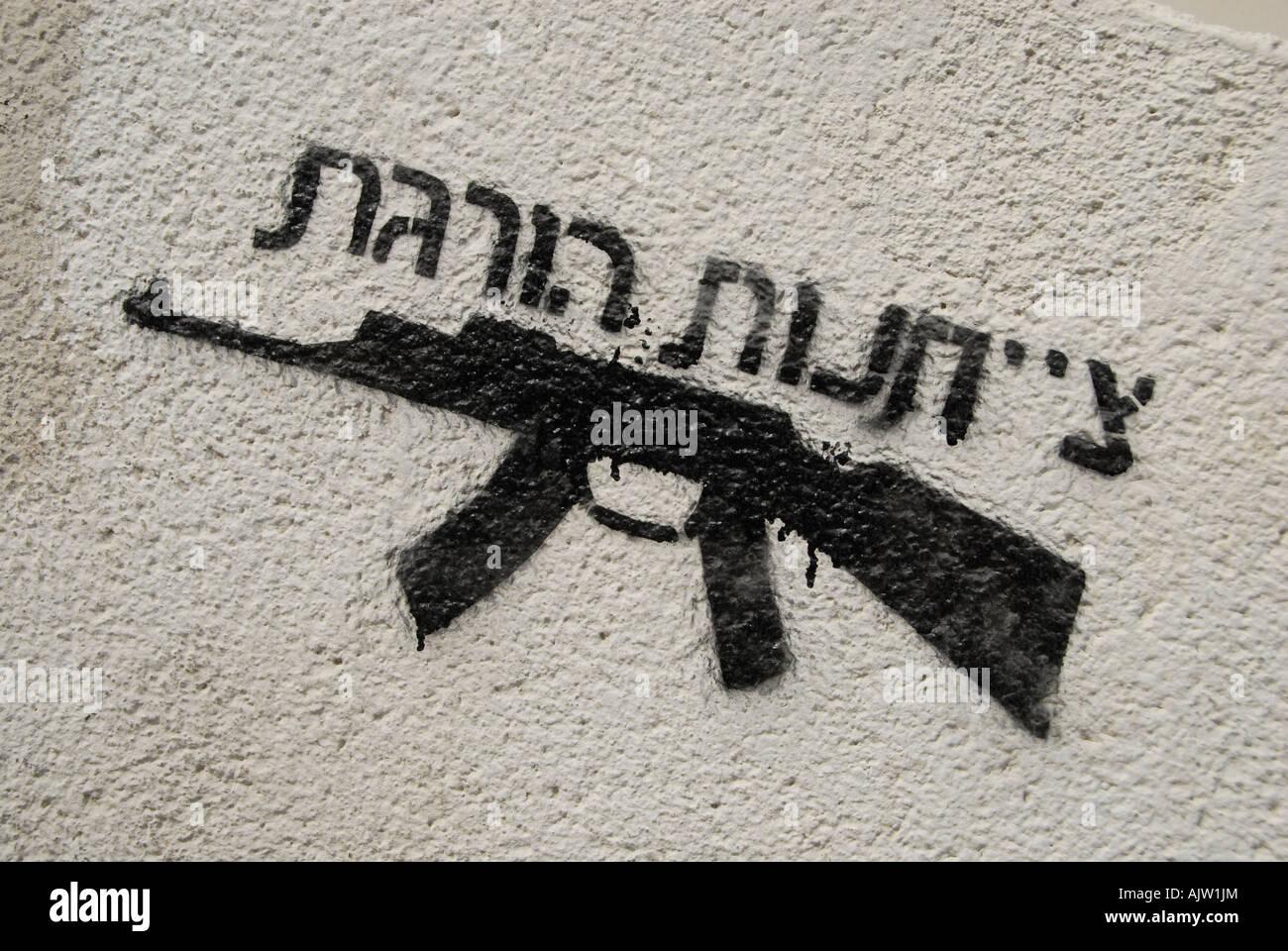 Spruzzato graffiti di un AK-47 Kalashnikov mitragliatrice con un messaggio scritto in ebraico che legge' obbedienza Immagini Stock