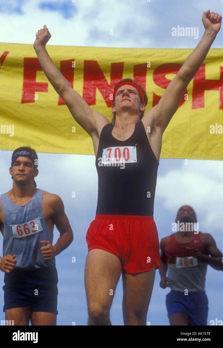 L'uomo attraversa il traguardo precedendo di altri runner Immagini Stock