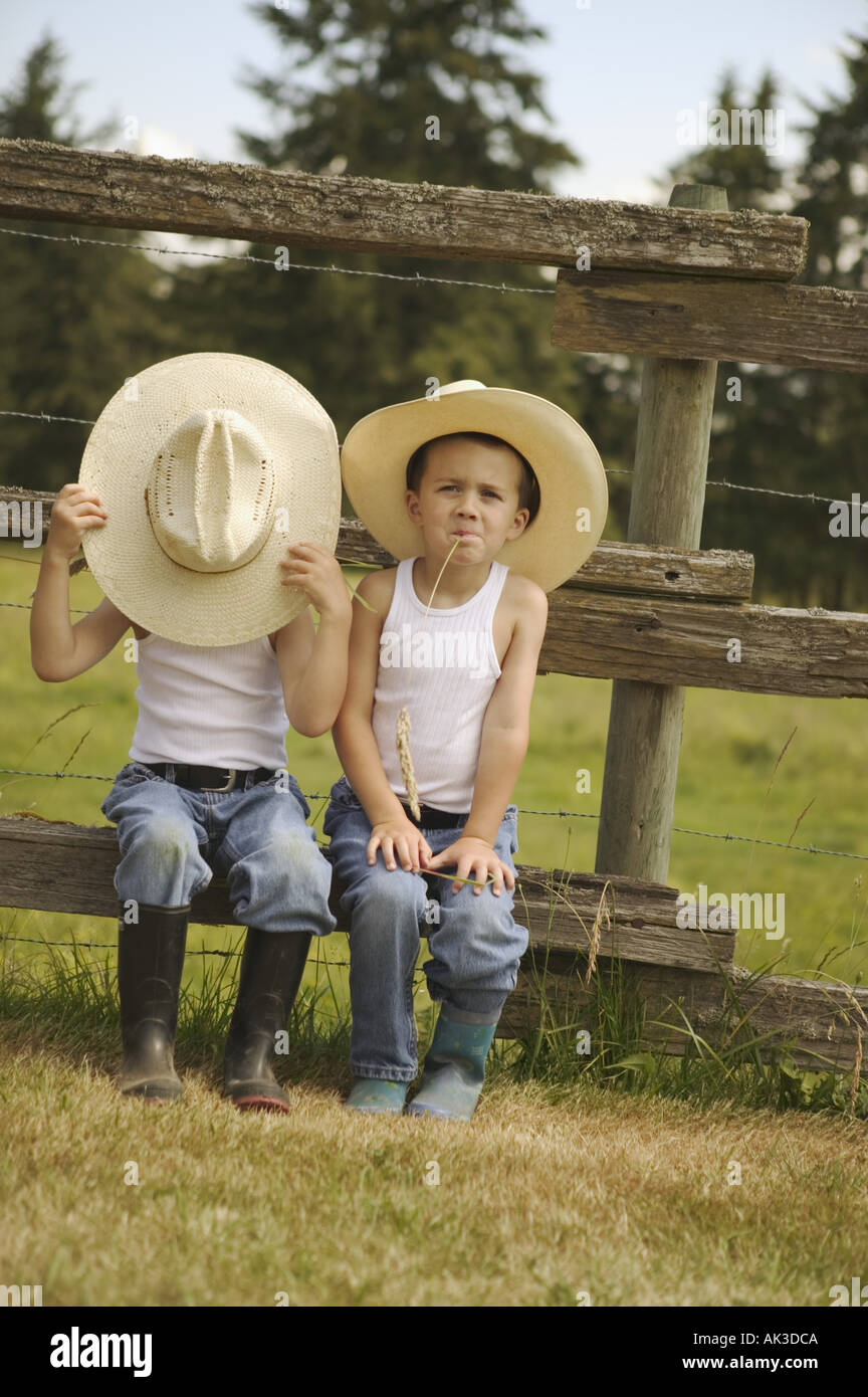 Twin boys in cappelli da cowboy seduto su una recinzione Immagini Stock fb56b0a6ce14