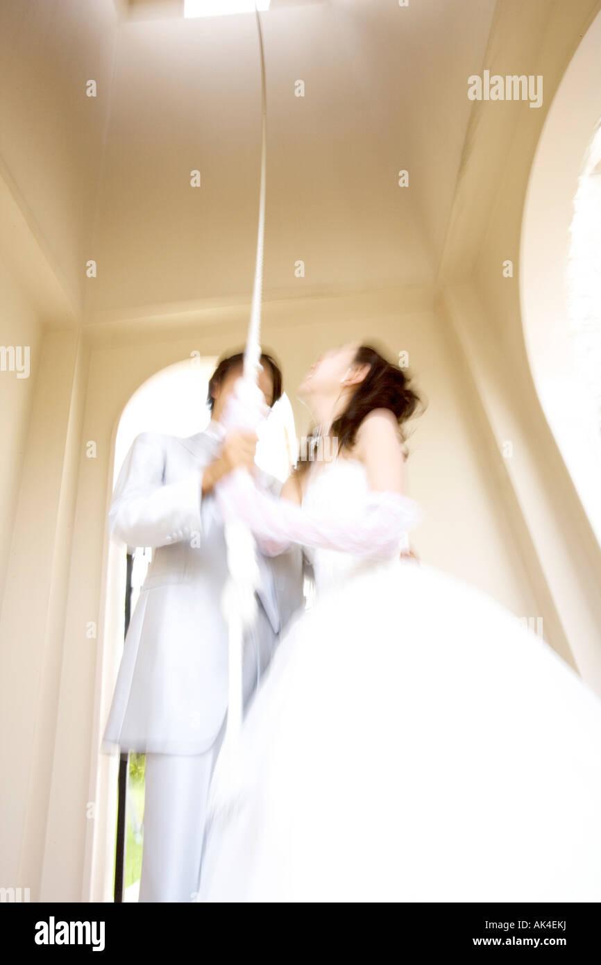 Sposa e lo sposo tirando la corda della campana Immagini Stock