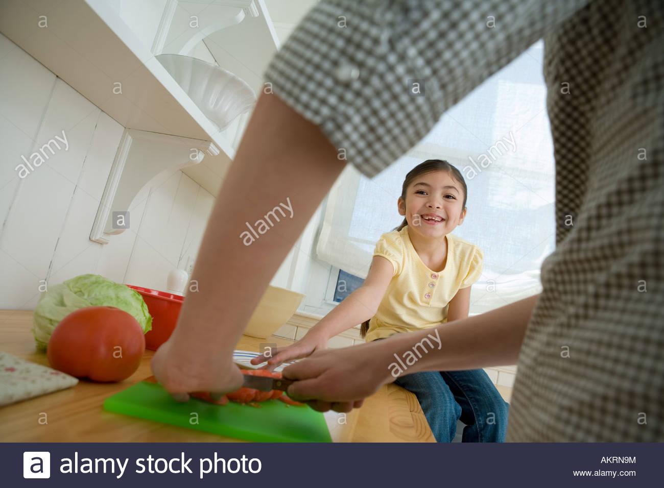 Una ragazza sedeva su un banco di cucina Immagini Stock