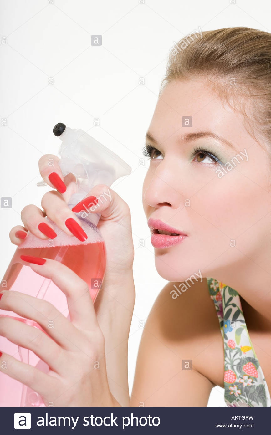 La donna la spruzzatura di liquido di pulitura Immagini Stock