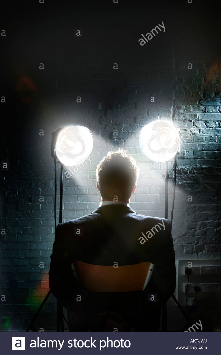 Scena di interrogazione con faretti che brilla in un il volto dell'uomo - Vista posteriore del sobrio uomo d Immagini Stock