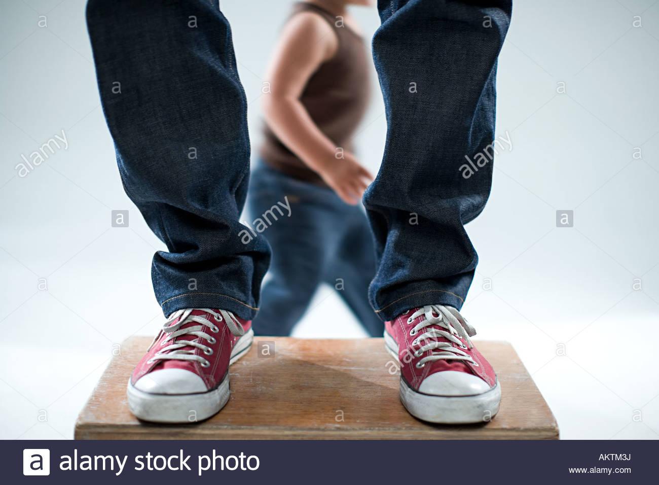Bambino e gambe di adulto Immagini Stock