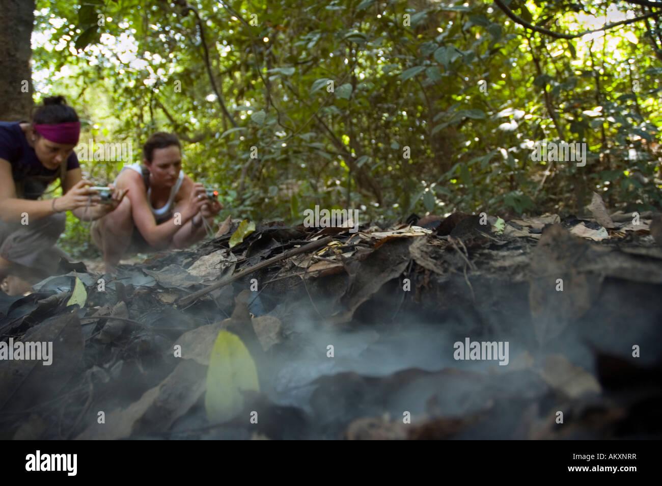 I turisti fotografare fumo che sale da cucina nel Tunnel di Cu Chi in Vietnam Immagini Stock