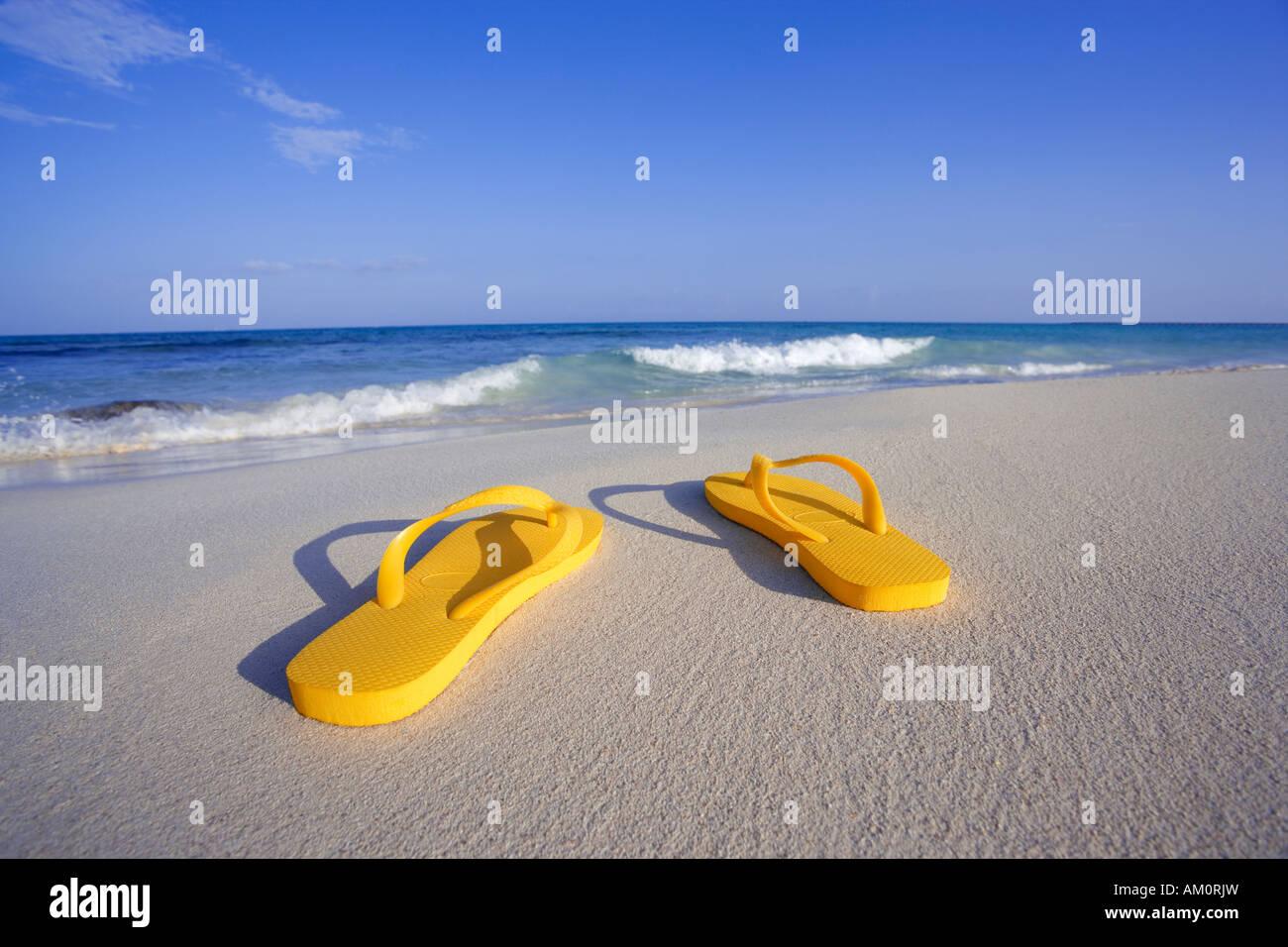 Coppia di giallo flip flop sandals sulla spiaggia vicino waters edge in Playa del Carmen, Messico Immagini Stock