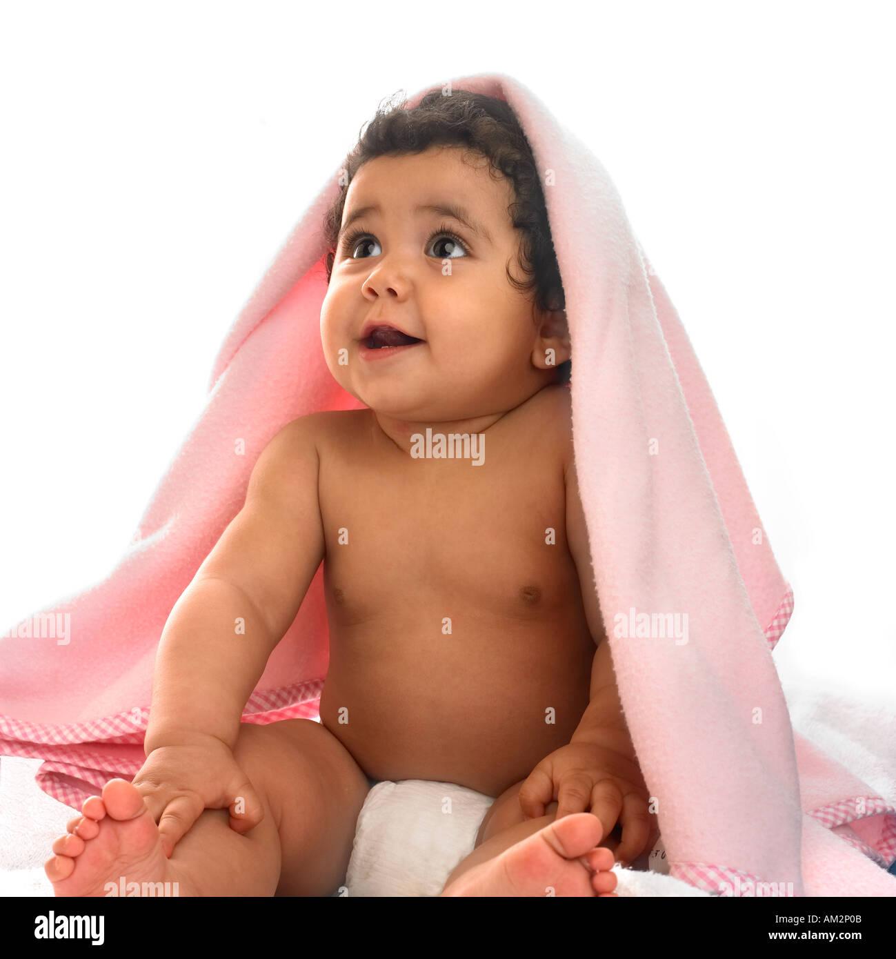Un simpatico baby sorrisi da sotto una coperta di lana sopra la sua testa Immagini Stock