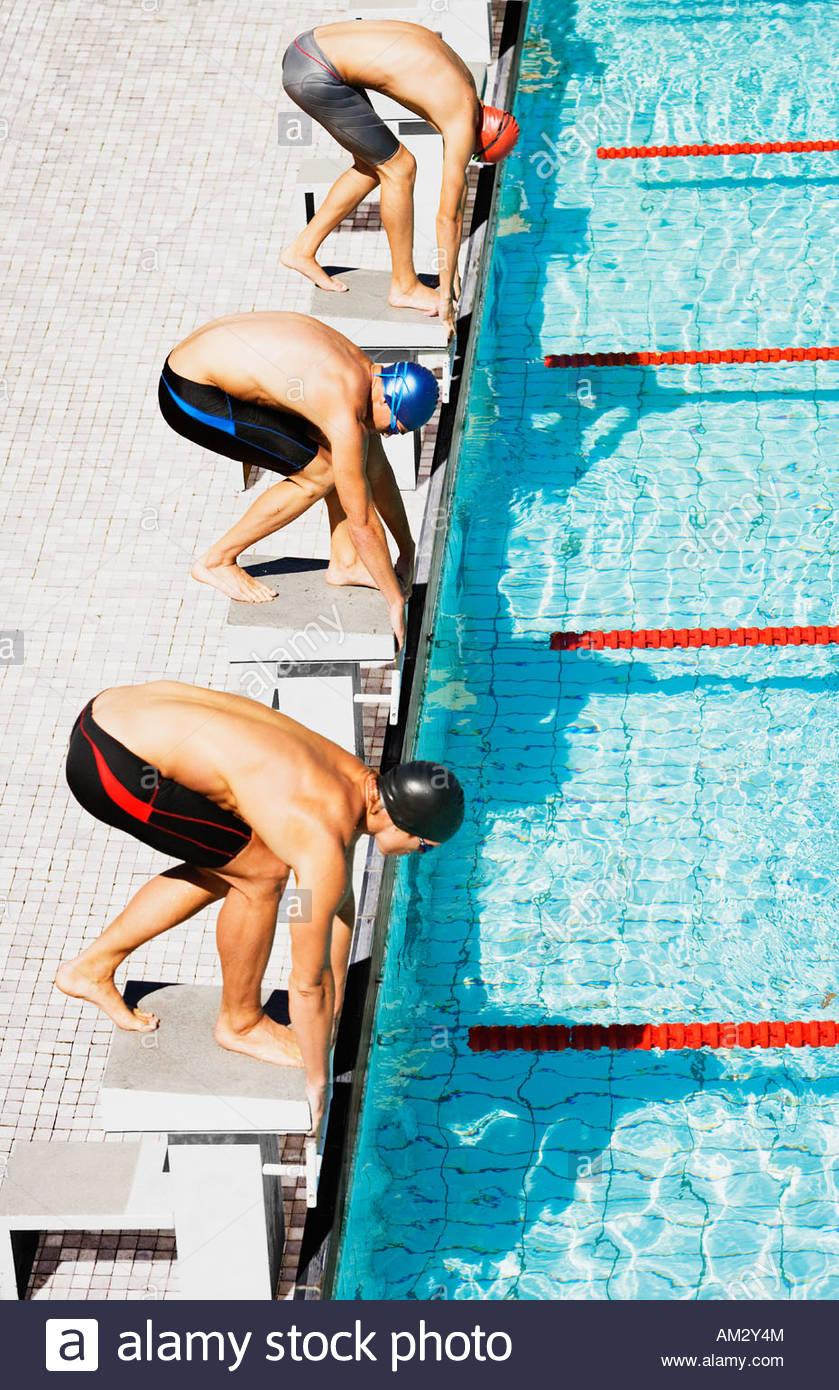Tre nuotatori su pool di blocchi di avvio Immagini Stock