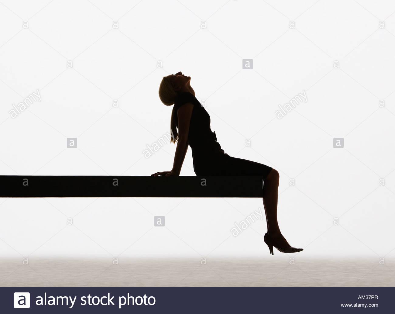 Donna seduta sul bordo del listone rilassante Immagini Stock