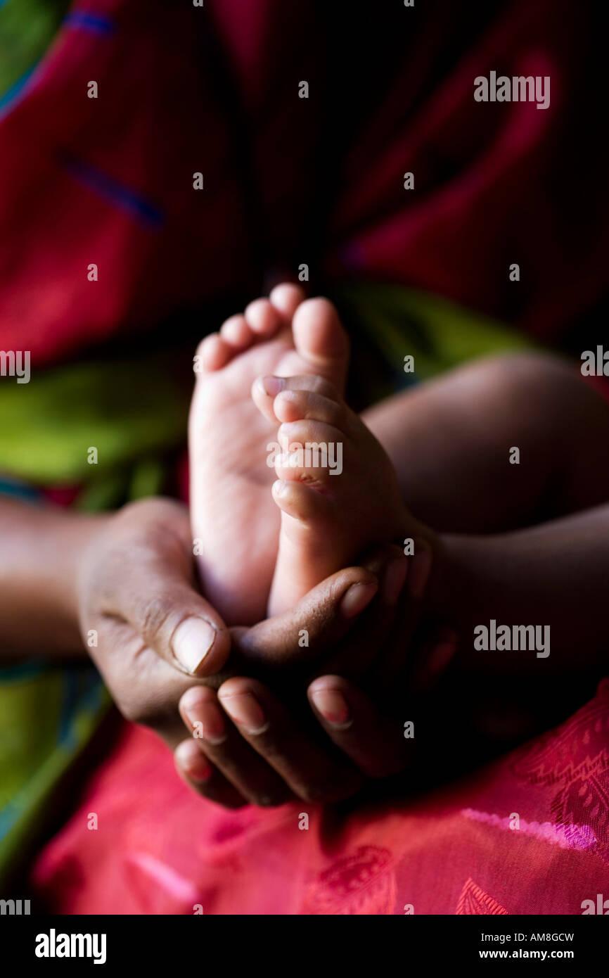 Madre indiana tenendo i bambini a piedi nudi. India Immagini Stock