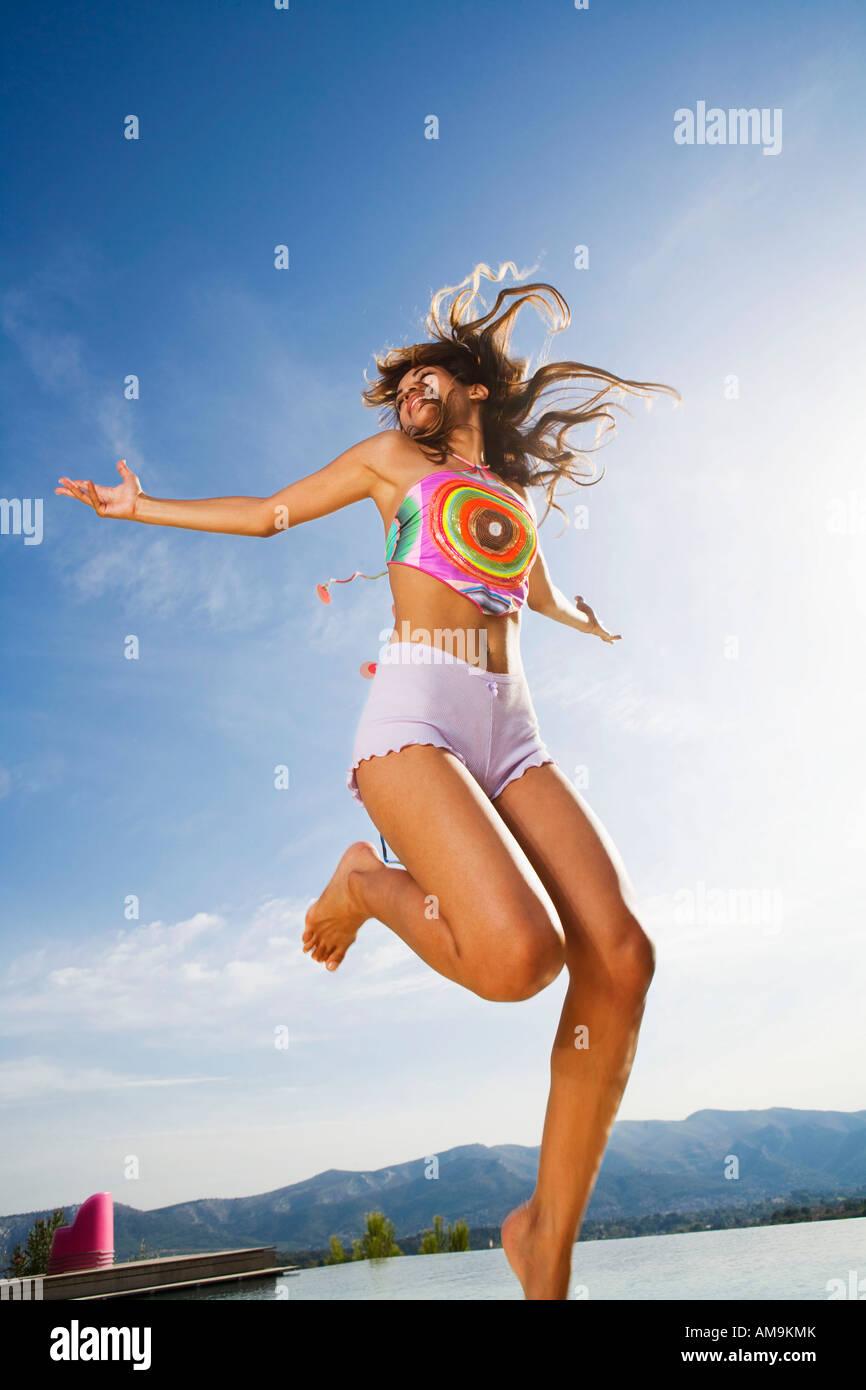 Donna salta in aria braccia che indossano pantaloncini all'esterno. Immagini Stock