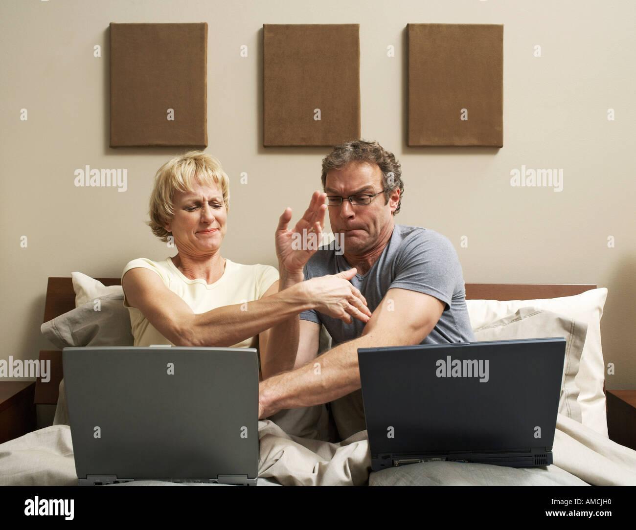 Giovane con laptop a letto Foto Stock