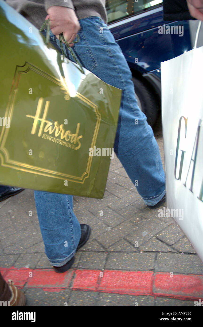 Harrods shopping bag essendo portati in Kensington Londra Immagini Stock