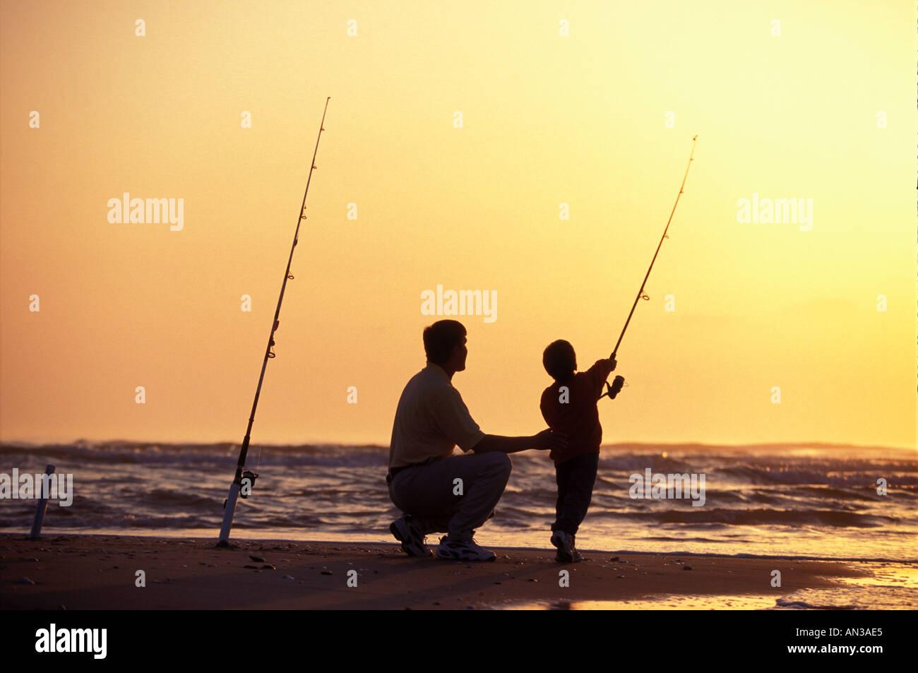 Padre ad insegnare la sua sonTo pesce surf sulla spiaggia in Carolina del Nord Immagini Stock