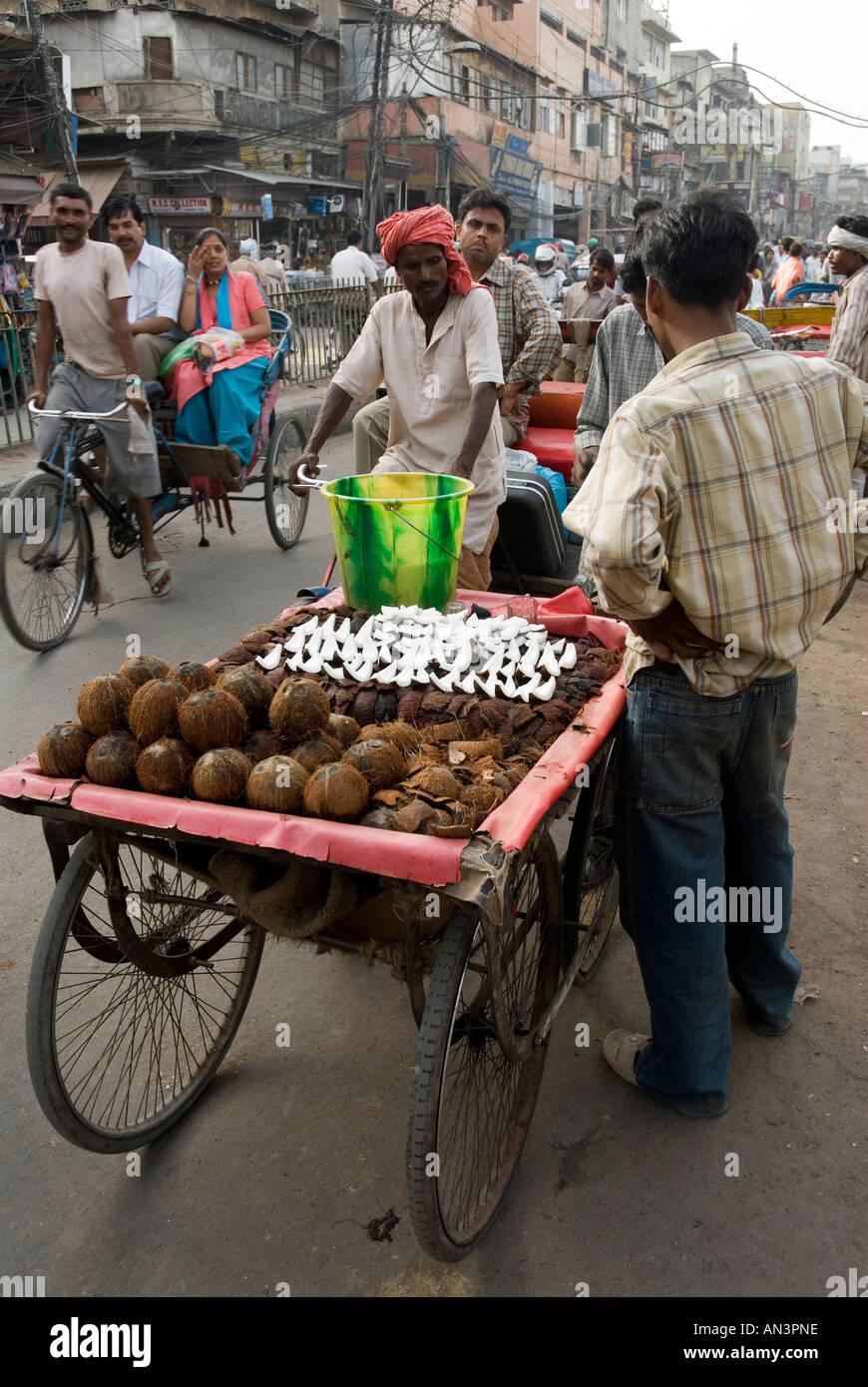 Vista posteriore di cocco fresco venditore nelle strade caotiche di Delhi Immagini Stock