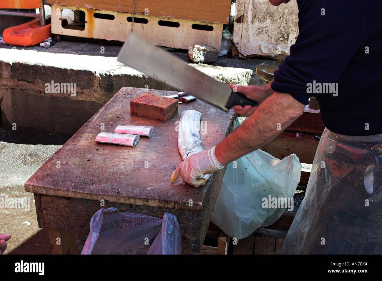 Un pescivendolo utilizza una mannaia di grandi dimensioni per il taglio di un grande pesce sciabola Immagini Stock