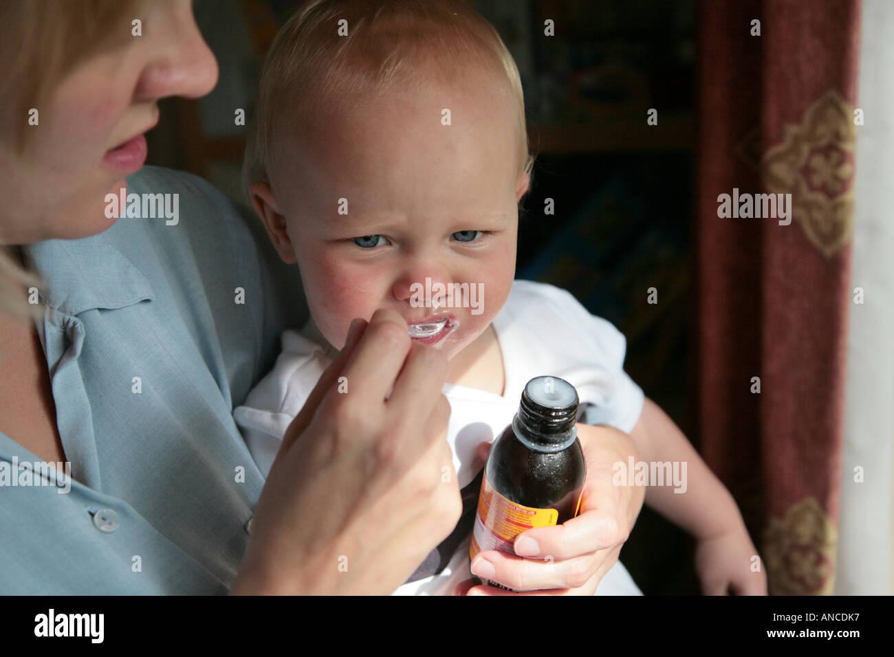 Baby essendo dato cucchiaio di medicina Immagini Stock