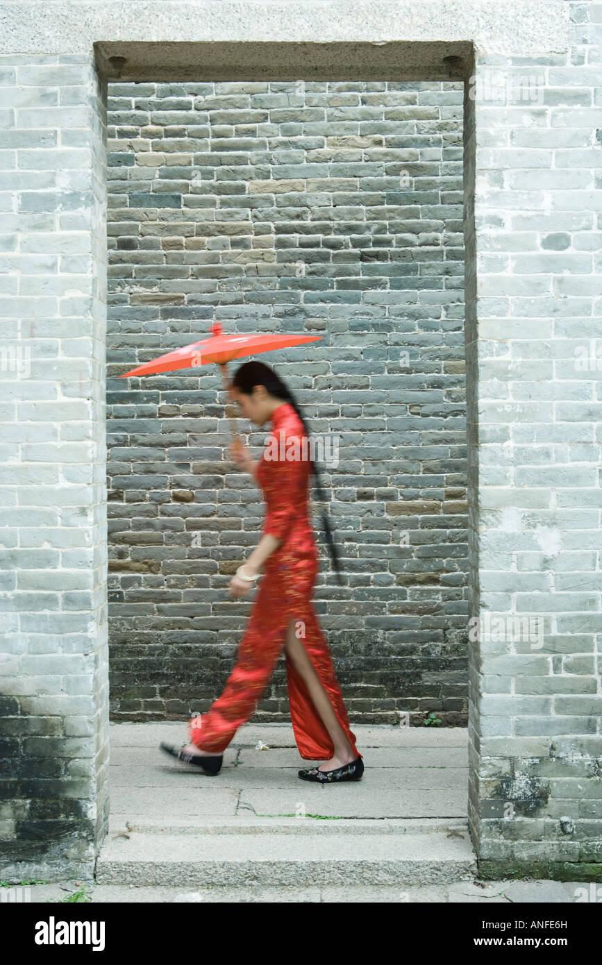 Giovane donna che indossa il cinese tradizionale abbigliamento, camminando con ombrellone, vista laterale, movimento Immagini Stock