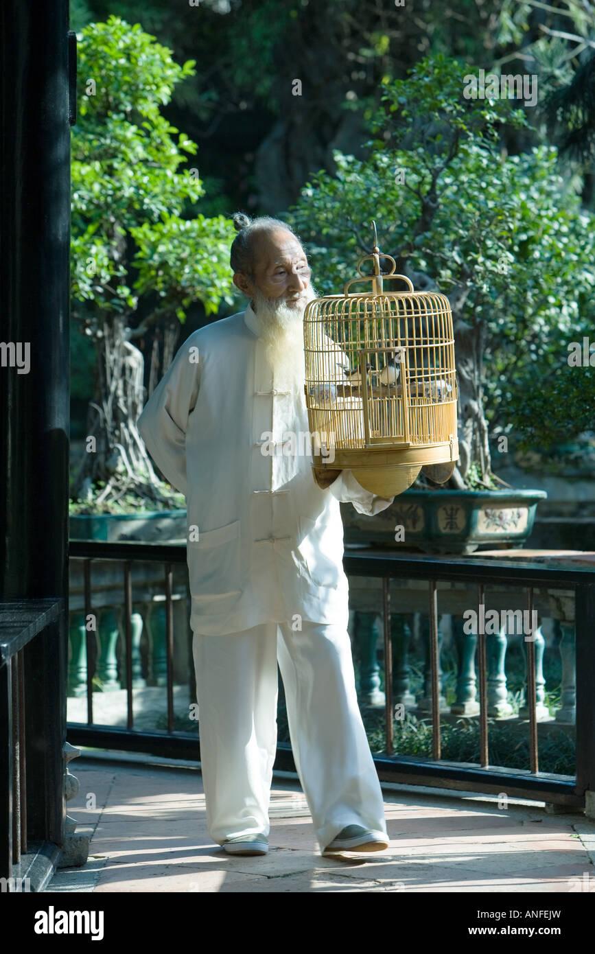 Uomo anziano che indossa il cinese tradizionale abbigliamento, portando la gabbia di uccelli Immagini Stock