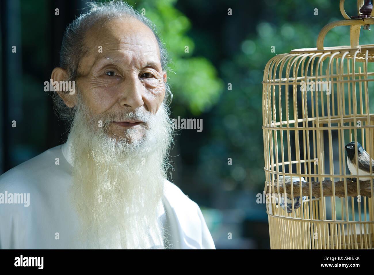 Uomo anziano che indossa il cinese tradizionale abbigliamento, con Bird Cage, ritratto Foto Stock