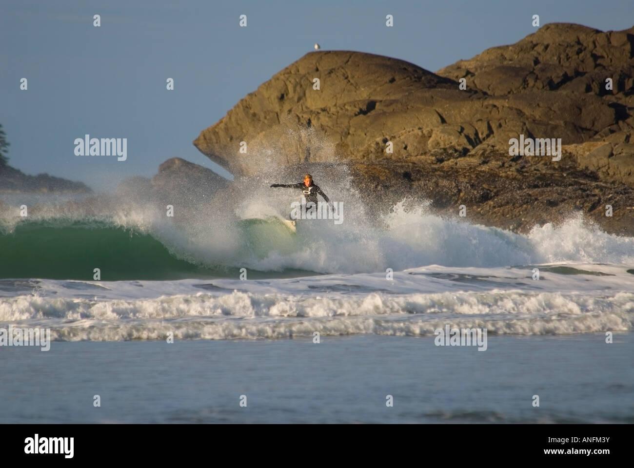 Un surfista sfide gli interruttori a Cox Bay, vicino a Tofino, sulla costa occidentale dell'isola di Vancouver, Foto Stock
