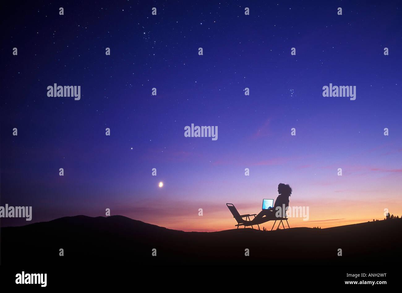 Utilizzando un computer portatile su una stella riempito di notte, British Columbia, Canada. Immagini Stock