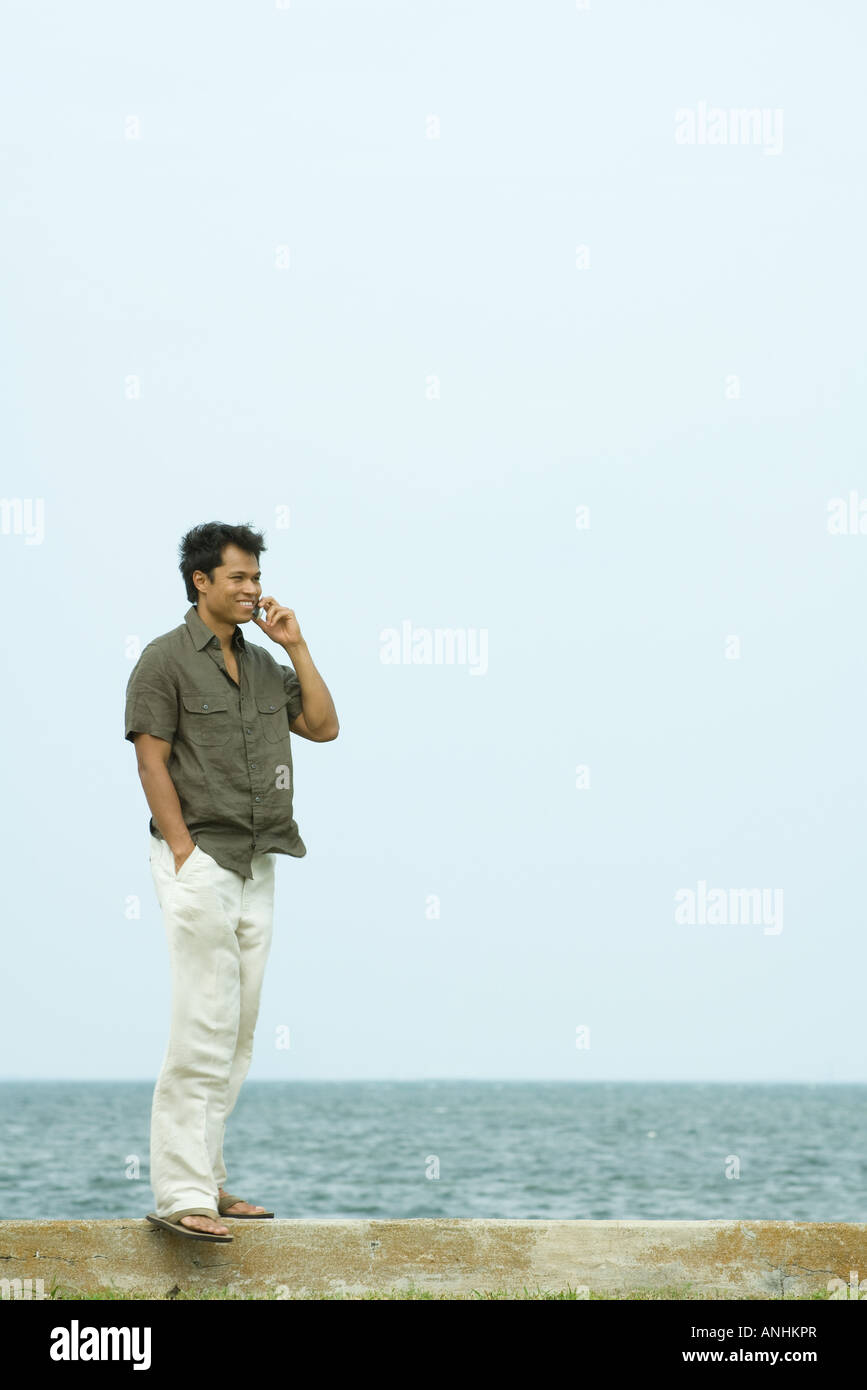 Uomo in piedi tramite telefono cellulare, oceano in background Immagini Stock