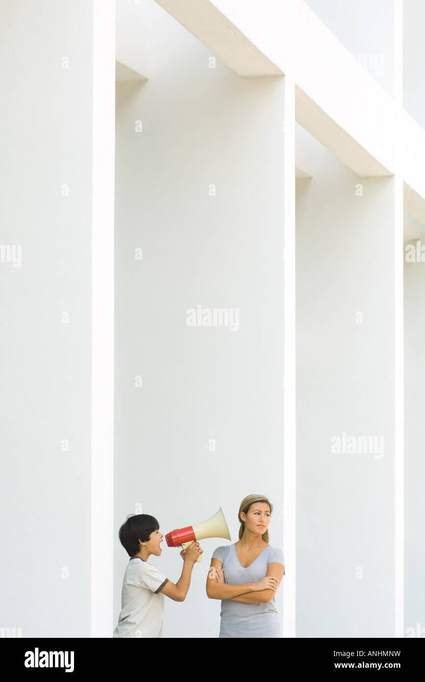 Boy utilizzando megafono per gridare a donna, donna manine e guardando lontano Immagini Stock