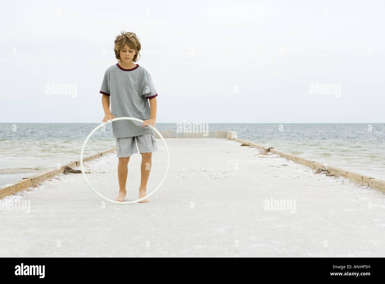 Ragazzo in piedi sul molo giocando con il cerchio di plastica a piena lunghezza Immagini Stock