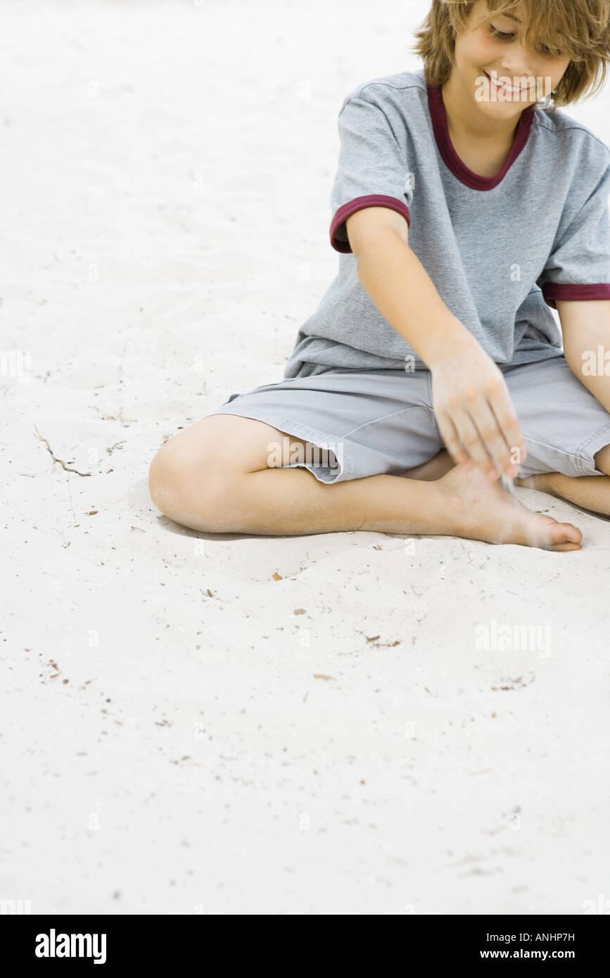 Ragazzo giocando in sabbia, sorridente, vista ritagliata Immagini Stock