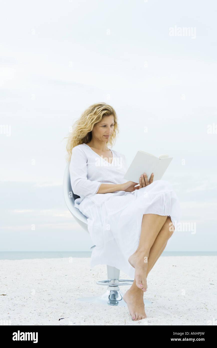 Donna seduta in sedia a sdraio alla spiaggia, libro di lettura Immagini Stock