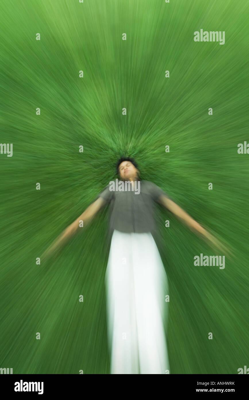 Uomo disteso sulla schiena in erba con gli occhi chiusi, movimento sfocato Immagini Stock