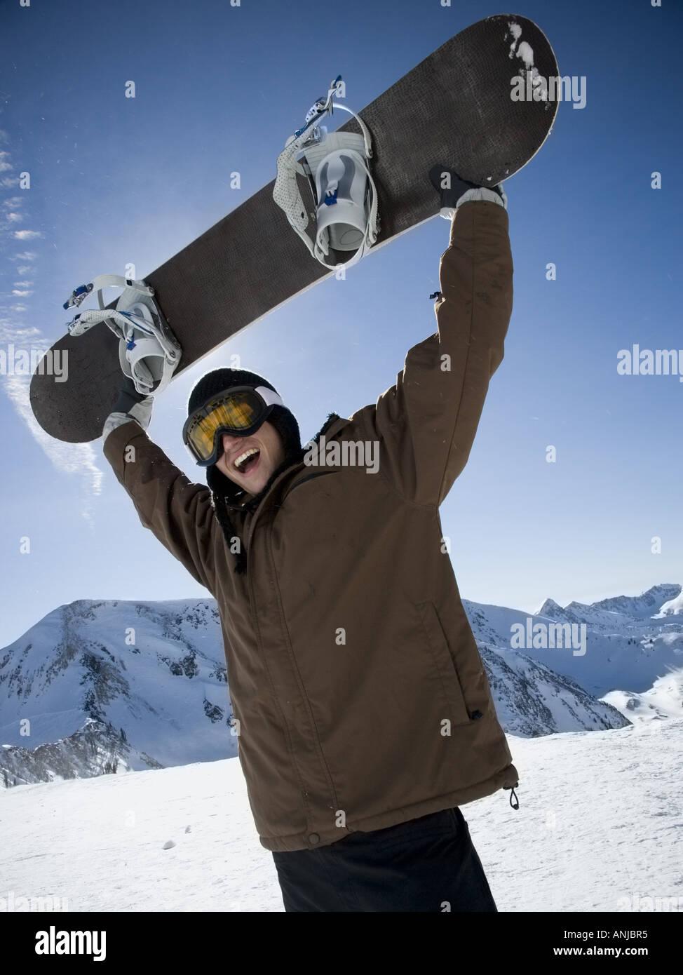 Basso angolo di visione di un giovane uomo di sollevamento di uno scarpone da snowboard e urlando Immagini Stock