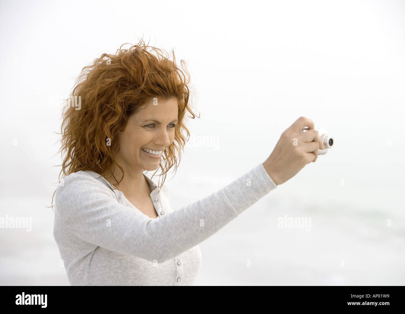 Donna che utilizza una fotocamera digitale Immagini Stock