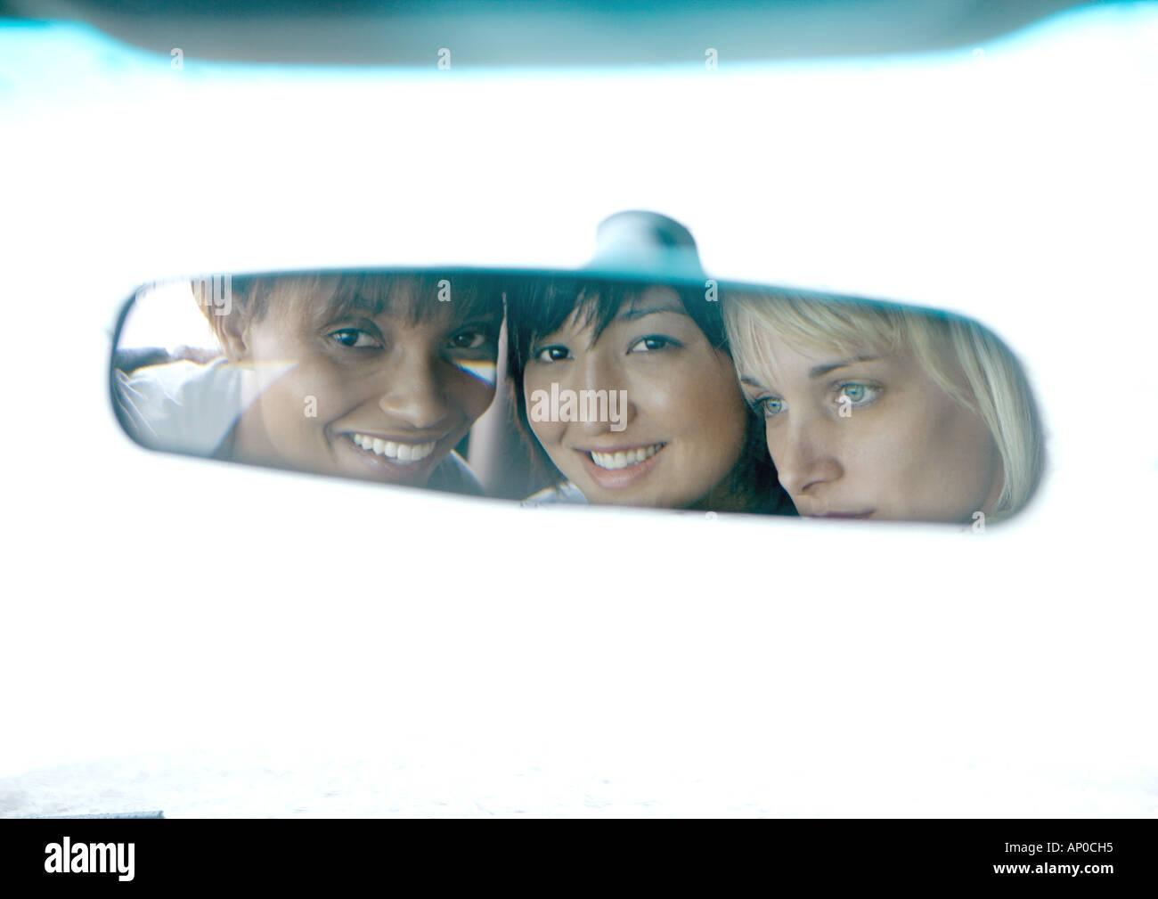 Tre giovani donne, volti riflessi in specchietto retrovisore Immagini Stock