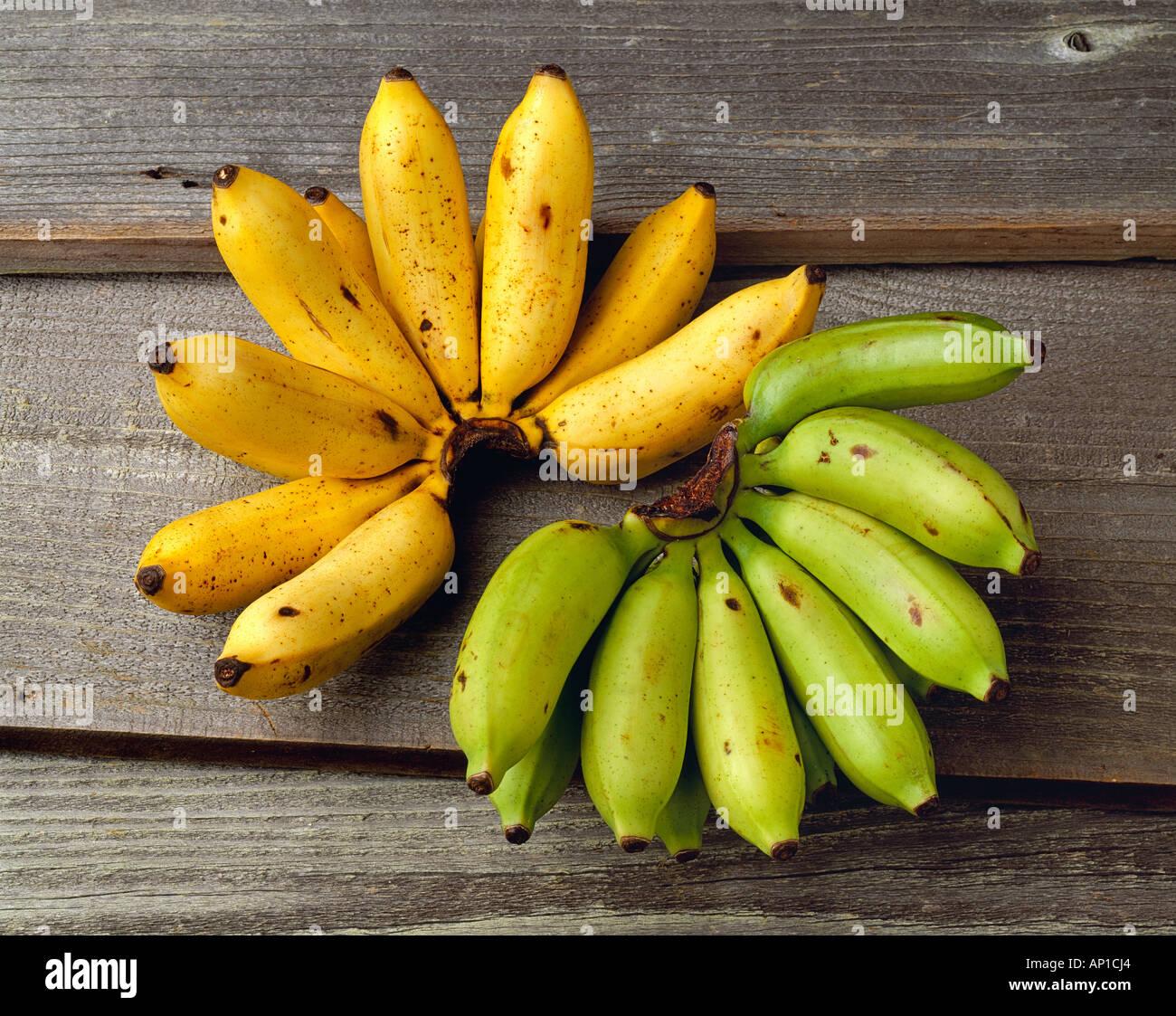 Agricoltura - Apple banane, un grappolo maturo e un mazzetto di verde e su di una superficie di barnwood, in studio. Immagini Stock