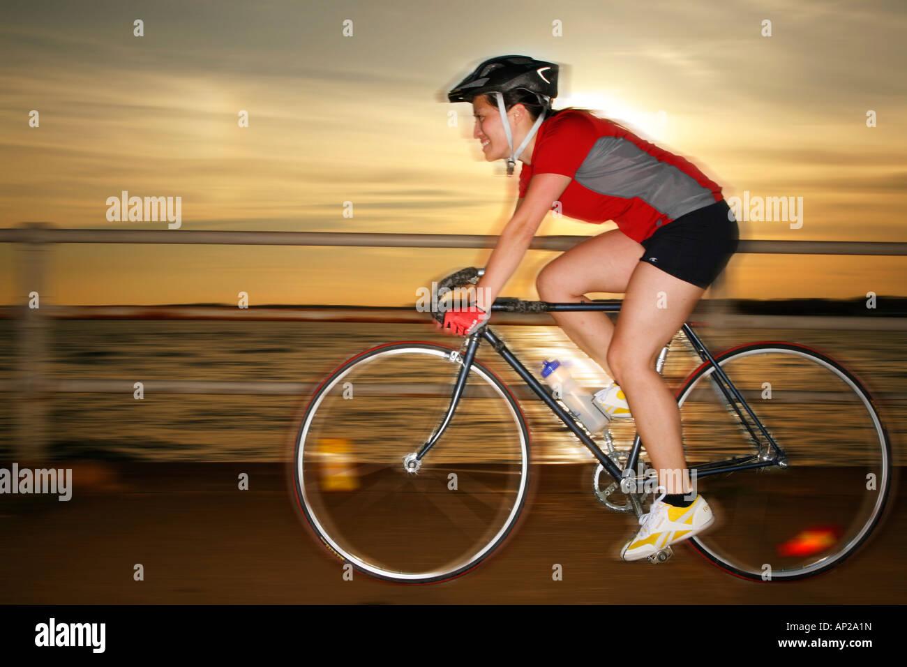 Giovane donna di 26 anni equitazione Bicicletta tramonto, signor-09-30-2007 Immagini Stock