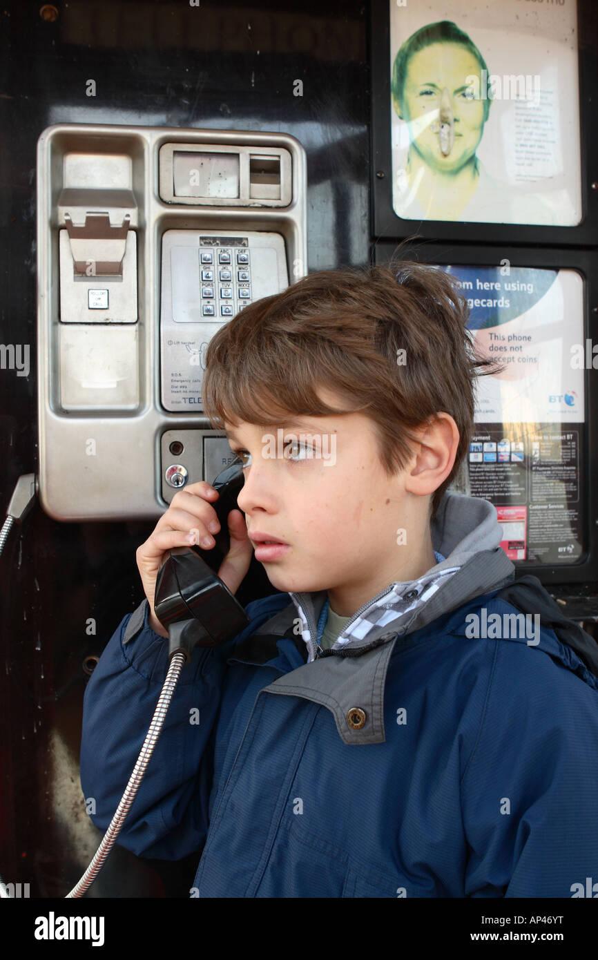 Ragazzo di 11 anni utilizzando un telefono pubblico in una callbox all'anello home cerca infelice POSTE DAL Immagini Stock