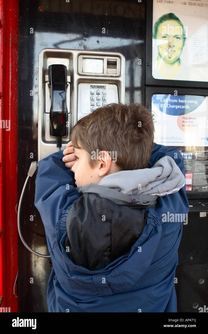 Ragazzo giovane di età compresa tra 11 anni infelice triste preoccupato runaway all'interno di un telefono Immagini Stock