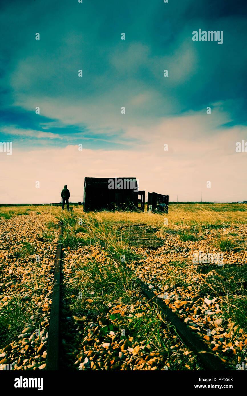 Uomo in piedi accanto a shack su una spiaggia Immagini Stock